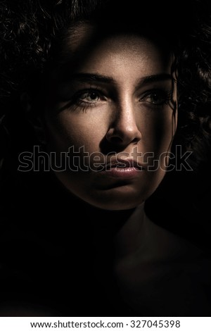 Young beautiful woman in dark shadow and ray of light - stock photo