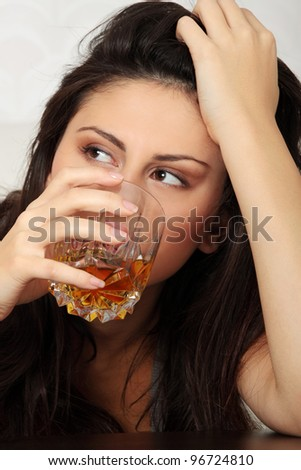 Young beautiful woman in depression, drinking alcohol - stock photo