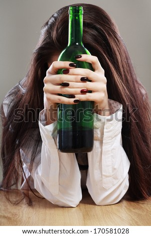 Young beautiful woman in depression, drinking alcohol hold bottle in her hands and hiding her face - stock photo