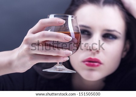 Young beautiful woman in depression, drinking alcohol on dark background. Focus on the glass - stock photo