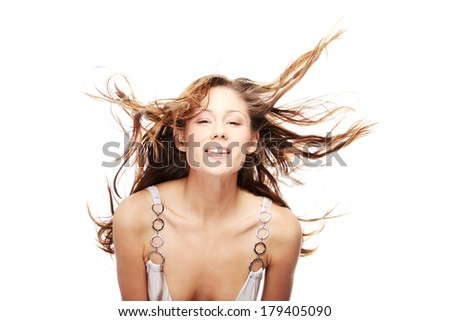 Young beautiful woman in elegant, evening, white dress dancing with wind (hair blowing), isolated on white background.  - stock photo