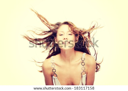 Young beautiful woman in elegant, evening, white dress dancing with wind (hair blowing), isolated on white background.