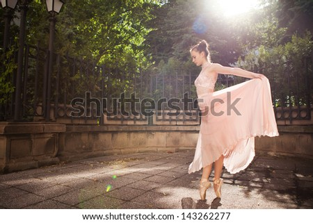 Young beautiful woman in elegant pink dress and ballet shoes in the garden.