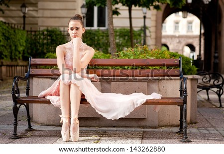 Young beautiful woman in elegant pink dress and ballet shoes on bench in the garden. - stock photo
