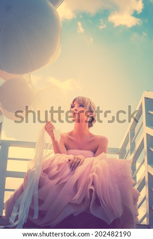 young beautiful woman in elegant wedding dress hold balloons sitting on  white stairs against sky with clouds, retro colors - stock photo
