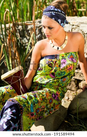 Young beautiful woman in ethnic dress with drum  - stock photo