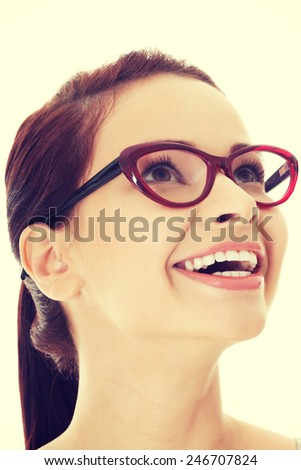 Young beautiful woman in eyeglasses looking up and smiling. - stock photo