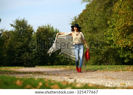Young beautiful woman in fashion blue ripped jeans and red bag walking in autumn park