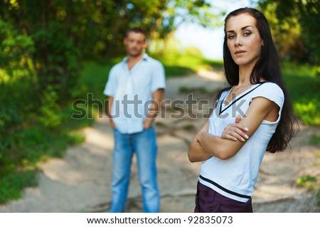 Young beautiful woman in foreground in summer solar park. Man stands behind in the distance.