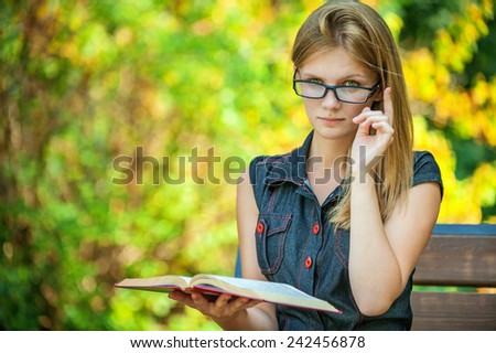 Young beautiful woman in glasses reads book in summer city park - stock photo
