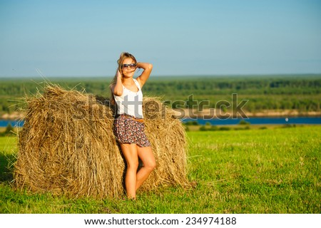 young beautiful woman in glasses standing on a green meadow against a haystack - stock photo