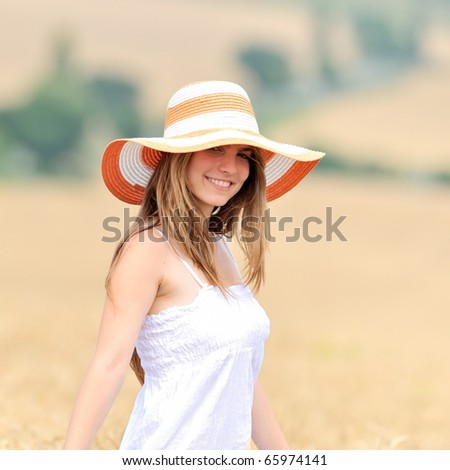 young beautiful woman in golden wheat field - stock photo