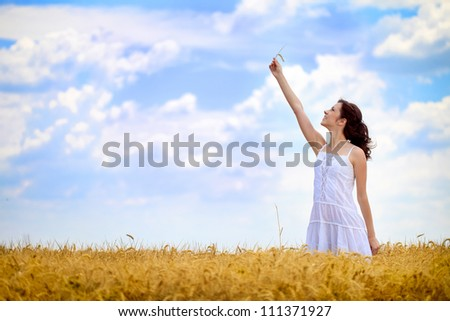 Young beautiful woman in golden wheat field in summer