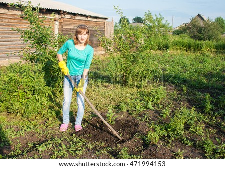 young beautiful woman in green blouse and blue jeans weeding potato sprouts using hoes outdoor on summer day