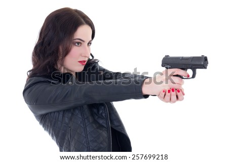 young beautiful woman in leather jacket shooting with gun isolated on white background - stock photo