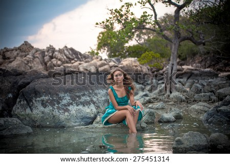 Young beautiful woman in long turquoise dress sitting on a stone by the sea - stock photo