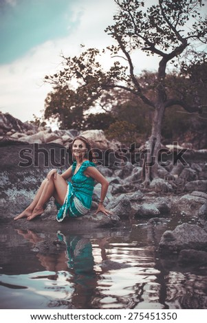 Young beautiful woman in long turquoise dress sitting on a stone by the sea. Retro colors