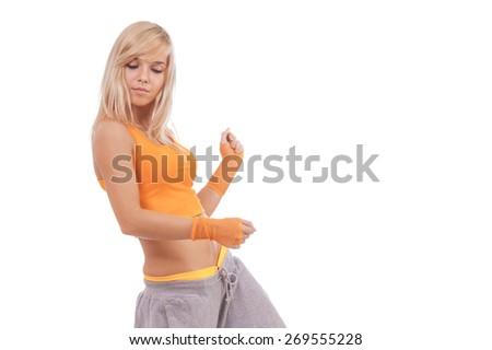 Young beautiful woman in orange clothes doing fitness isolated on white background. - stock photo