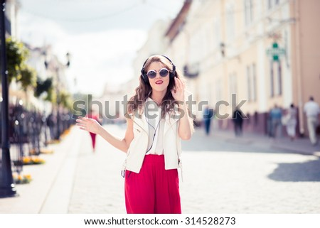 Young beautiful woman in outfit enjoying the music