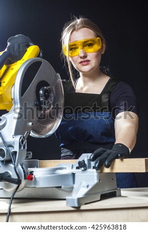 young beautiful woman in overalls and glasses with disk saw preparing for cutting. Photo on black background. close-up portrait. - stock photo