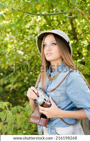 Young beautiful woman in pith hat taking pictures on retro camera on green trees summer copy space background - stock photo