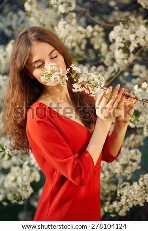 Young beautiful woman in red dress enjoying smell of blooming tree on a sunny day. Close eyes