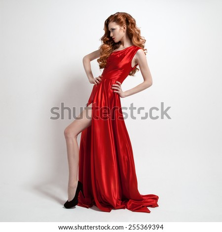 Young beautiful woman in red dress. White background. - stock photo