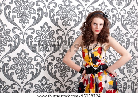 Young beautiful woman in retro dress on vintage wallpaper background - stock photo