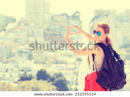 Young beautiful woman in San Francisco making hand shaped heart on spring summer warm sunny day. Girl with sunglasses happy outdoors. Instagram style image with yellow filter - stock photo