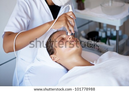 Young beautiful woman in spa clinic making face treatment - stock photo