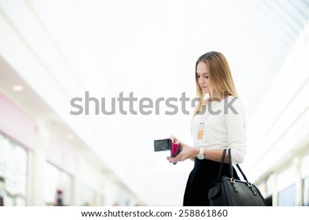 Young beautiful woman in stylish clothes with leather handbag checking her wallet in shopping center. Copyspace - stock photo