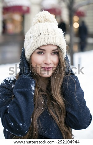 Young beautiful woman in stylish dark gray wool coat on a background of a winter street - stock photo