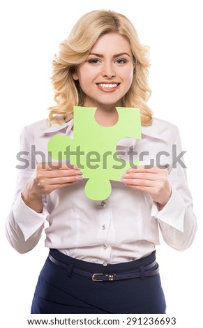 Young beautiful woman in suit holding piece of puzzle and smiling to camera.