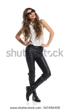 Young beautiful woman in sunglasses, black leather trousers, boots and white shirt standing with legs crossed and posing with hands on hip. Full length studio shot isolated on white. - stock photo