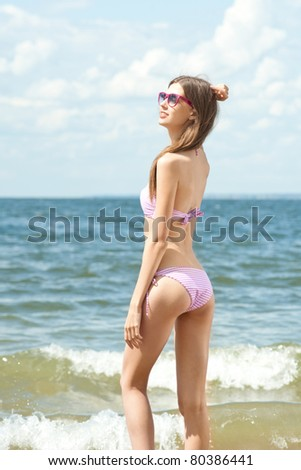Young beautiful woman in swimsuit and sunglasses on the beach - stock photo