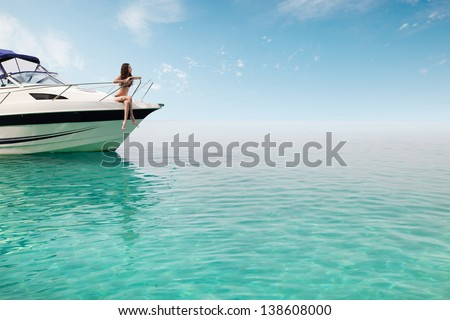 Young beautiful woman in swimsuit sitting on yacht at sunny summery day and looking to a blue sea - stock photo