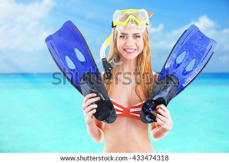 Young beautiful woman in swimsuit with diving mask and flippers on blurred sea background - stock photo