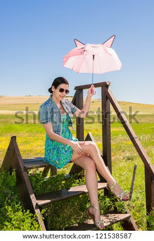 Young beautiful woman in the flower field with pink umbrella, selective focus, during day