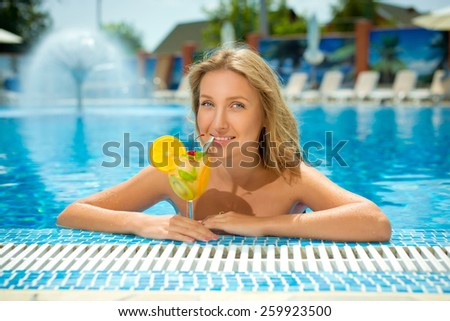 Young beautiful woman in the pool with a cocktail. Summer. Model. - stock photo