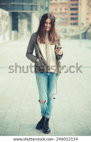 young beautiful woman in town listening music headphones