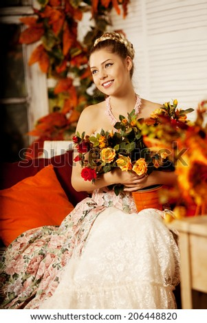 Young beautiful woman in vintage dress on autumn porch. Beauty girl in fall orange leaves