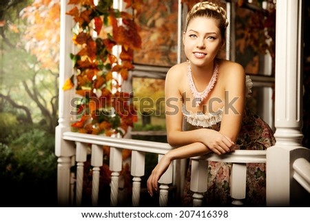 Young beautiful woman in vintage dress on autumn porch. Beauty girl in fall orange leaves - stock photo