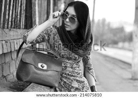 Young beautiful woman in warm clothes and glasses with brown leather retro bag looking into the distance posing outdoors. Season Autumn Winter 2014. Fashion model shooting. Black and white image.  - stock photo