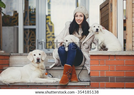 young beautiful woman in warm clothes with white labrador retrievers. dogs and woman. outdoor portrait. Pets and girl. Beautiful woman playing with her dog. Outdoor portrait. series - stock photo