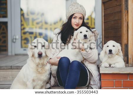 young beautiful woman in warm clothes with white labrador retrievers. dogs and woman. outdoor portrait. Pets and girl. Beautiful woman playing with her dogs, Puppy