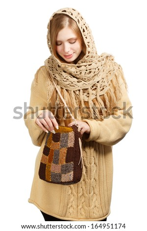 Young beautiful woman in warm winter clothing with knitted bag standing isolated on white background - stock photo