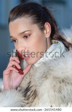 Young beautiful woman in white coat with fur collar talking on mobile phone.