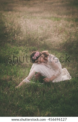young beautiful  woman in white lacy dress hold bouquet of wild flowers sit  on meadow full body shot