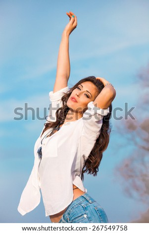 young beautiful woman in white shirt and blue jeans enjoy in sunny day, blue sky in background - stock photo