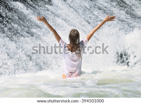 Young beautiful woman in white wet dress standing in the water at the waterfall. - stock photo